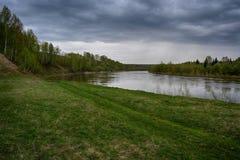 Fantastische rivier met vers groen gras in het zonlicht Royalty-vrije Stock Afbeeldingen