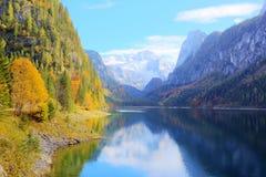 Fantastischer Herbstsonnenschein beleuchtet auf Gebirgssee Gosausee stockfoto