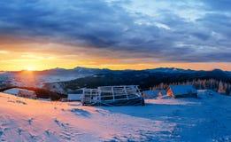 Fantastischer Sonnenuntergang über Schnee-mit einer Kappe bedeckten Bergen und hölzernen Chalets Lizenzfreie Stockfotografie