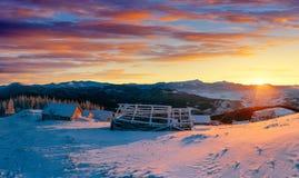 Fantastischer Sonnenuntergang über Schnee-mit einer Kappe bedeckten Bergen und hölzernen Chalets Lizenzfreie Stockbilder