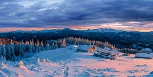 Fantastischer Sonnenuntergang über Schnee-mit einer Kappe bedeckten Bergen und hölzernen Chalets Lizenzfreies Stockbild