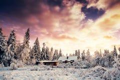 Fantastischer Sonnenuntergang über Schnee-mit einer Kappe bedeckten Bergen und hölzernen Chalets Lizenzfreie Stockfotos