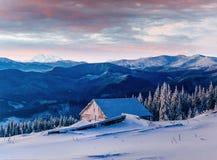 Fantastischer Sonnenuntergang über Schnee-mit einer Kappe bedeckten Bergen und hölzernen Chalets Stockfoto