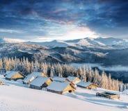 Fantastischer Sonnenuntergang über Schnee-mit einer Kappe bedeckten Bergen und hölzernen Chalets Stockfotos