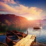 Fantastischer Sonnenuntergang auf einem See zwischen Bergen und Holz Stockfotografie