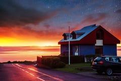 Fantastischer sternenklarer Himmel und ein Haus auf dem Strand Stockfotografie