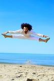 Fantastischer Tänzer, der in die Luft vor dem Ozean springt Stockfoto