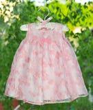 Fantastisches rosa Kleid, das an den Aufhängern auf dem Hintergrund des Fensters hängt. Stockbild