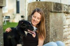 Fantastisk brunett med det charmiga leendet som utomhus spelar med hennes husdjur i parkera under solig sommardag royaltyfria bilder