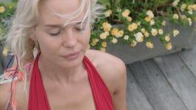 Fantastisk flicka i det röda baddräktsammanträdet i lotusblommapositionen på trägolvet stock video