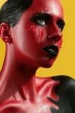 Fantastisk flicka med röd hud på en gul bakgrund och vita svarta kanter för tänder och Arkivbilder