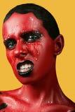Fantastisk flicka med röd hud på en gul bakgrund och vita svarta kanter för tänder och Royaltyfria Foton