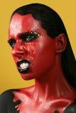 Fantastisk flicka med röd hud på en gul bakgrund och vita svarta kanter för tänder och Royaltyfri Foto