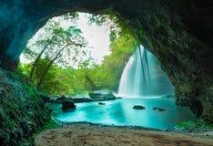 Fantastisk grotta i djup skog med härlig vattenfallbakgrund royaltyfri fotografi