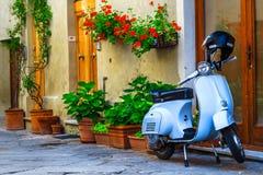 Fantastisk italiensk gata med färgrika blommor och sparkcykeln, Pienza, Tuscany royaltyfri bild