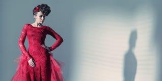 Fantastisk kvinna som bär den fashionbable röda klänningen royaltyfria foton