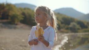 Fantastisk liten flicka som äter en banan nära sjön stock video
