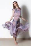 Fantastisk modekvinna i en flödande genomskinlig klänning med ljus makeup i studio fotografering för bildbyråer