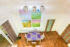 Fantastisk modern livingroomhemmiljö för exponeringsglaslokal för tätt bestick äta middag rund tabell upp Hu Arkivfoton