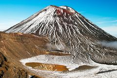 Fantastisk naturunder, den enorma aktiva vulkan med det röda maximumet ovanför sulfidvattensjön med spegelreflexion av snö täckte arkivfoto