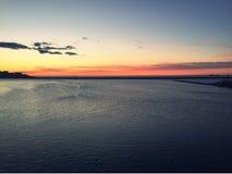 Fantastisk orange solnedgång, Adriatiskt hav och fyr Arkivfoton