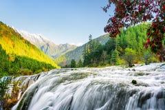 Fantastisk sikt av den pärlemorfärg stimvattenfallet bland berg Arkivfoto