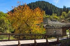Fantastisk sikt av kyrkan av antagandet, floden och höstträdet i stad av Shiroka Laka, Bulgarien royaltyfri foto