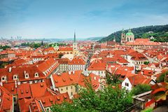 Fantastisk sikt av taken av byggnader och kyrkan av St Thomas i Prague uppifrån av St Nicholas Bell Tower Royaltyfria Foton