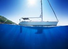 Fantastisk solljusseaview till segelbåten i det tropiska havet med djupblått under splitted av vattenlinje Royaltyfri Bild