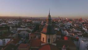 Fantastisk solnedgång över tak för röd tegelplatta av storstaden