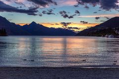 Fantastisk solnedgång på Wakatipu sjön som omges av härliga berg i Queenstown arkivbild