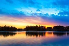Fantastisk solnedgånghimmelreflexion på floden Royaltyfri Foto