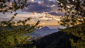 fantastisk solnedg?ng Sikt av v?rlandskap, solljus och m?rka moln ?ver arkivbilder