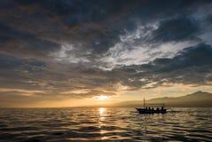 Fantastisk soluppgång med konturn av folk i litet fartyg i Lovin Royaltyfri Fotografi