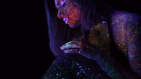 Fantastisk stående av den härliga modekvinnan med purpurfärgat hår i UV ljus för neon Modell Girl med fluorescerande idérikt stock video