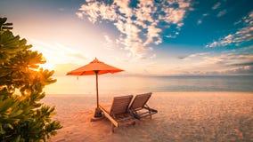 Fantastisk strandsolnedgång med solsängar och avslappnande lynne arkivfoton