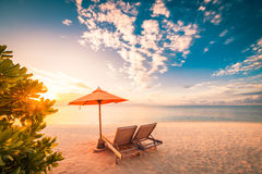 Fantastisk strandsolnedgång med solsängar och avslappnande lynne royaltyfri fotografi