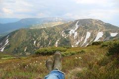 Fantastiska berg landskap, gräs med vita blommor och ben i kängor Royaltyfria Bilder