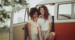 Fantastiska flickor afrikan och rödhårig man med lockigt hår som ser rakt till kameran och posera som beside står av a arkivfilmer