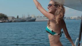 Fantastiska flickor kör på en yacht förbi havet och vinkar arkivfilmer