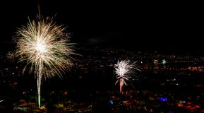 Fantastiska fyrverkerier över en stad vid natt royaltyfri bild