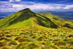 Fantastiska soliga kullar under blå himmel för morgon dramatisk liggande royaltyfri fotografi