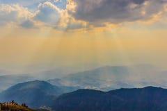 Fantastiska solstrålar som skiner till och med molnen, täcker berget Royaltyfri Bild