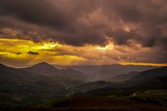 fantastiskt ?gonblick Mycket intressant solnedg?ng Sikt av v?rlandskap, solljus och m?rka moln ?ver royaltyfria bilder