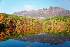 Fantastiskt höstsjölandskap av Kagami Ike Mirror Pond i morgonljus med symmetriska reflexioner av färgrik nedgånglövverk fotografering för bildbyråer