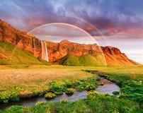 Fantastiskt landskap med en regnbåge och en vattenfall i Island royaltyfri bild