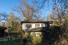 Fantastiskt landskap med träbron och det gamla huset i by av Bozhentsi, Bulgarien Fotografering för Bildbyråer