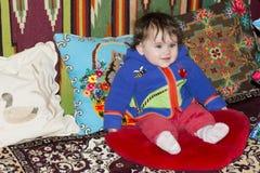 Fantastiskt liten flickasammanträde i säng på en säng med broderade kuddar arkivbilder