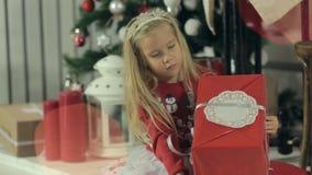 Fantastiskt liten flickasammanträde med hennes gåva nära stock video