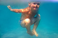 Fantastiskt lyckligt behandla som ett barn undervattens- pojkedykar Arkivfoto